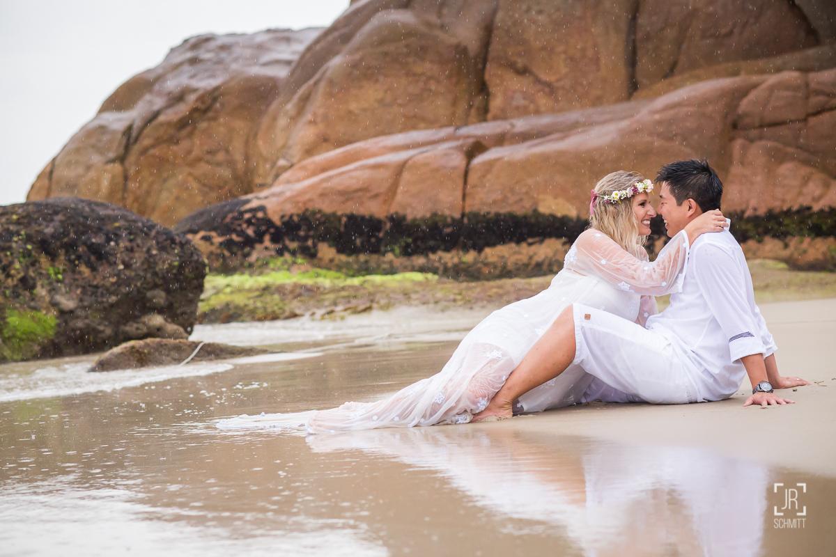 noiva deitada na areia da praia com vestido branco