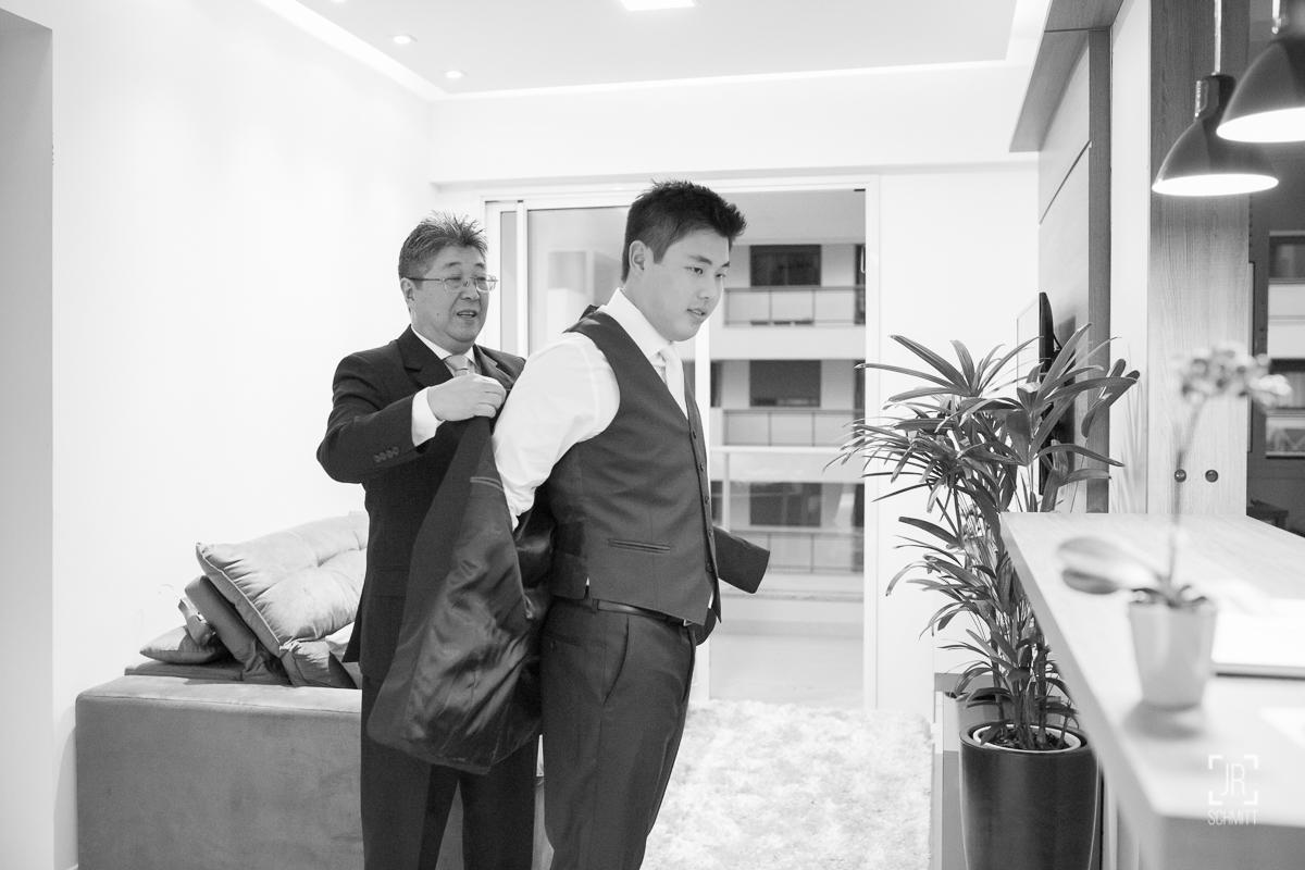 pai do noivo ajudando a vestir o terno