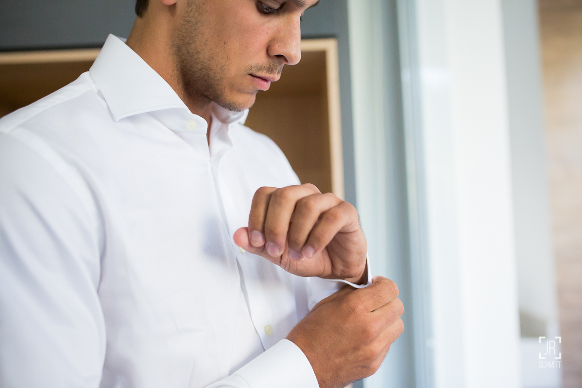 noivo abotoando a manga da camisa