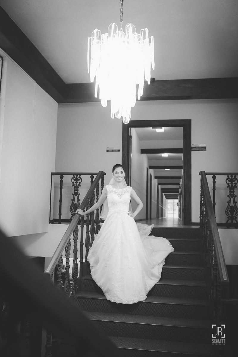 Noiva posando na escadaria com lustre