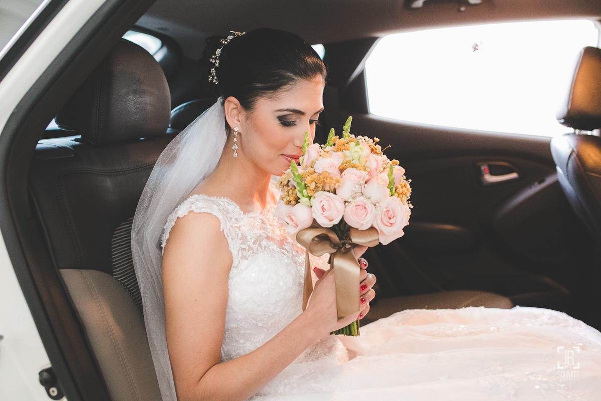 Noiva cheirando o buquê de rosas