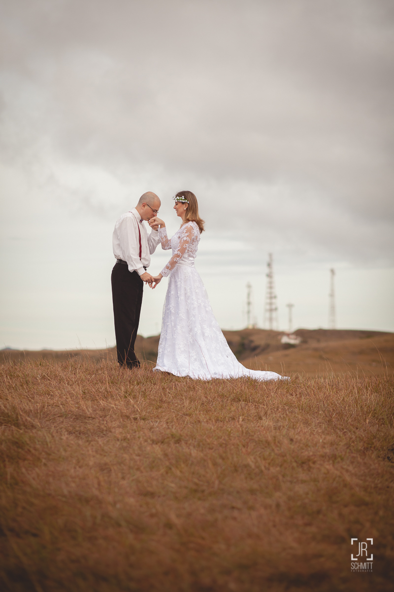 Sessão trash the dress, noivo beijando a mão da noiva