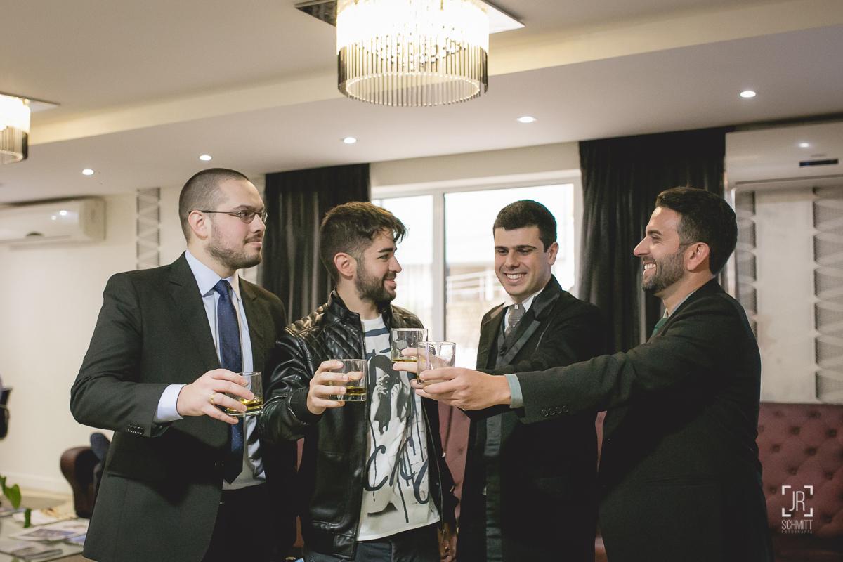 noivo brindando com padrinhos no hall do hotel