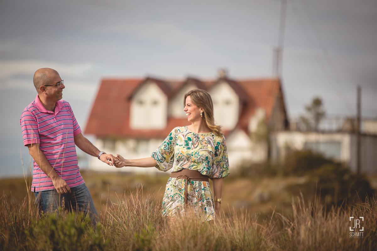 Casal de mãos dadas com casa de fundo