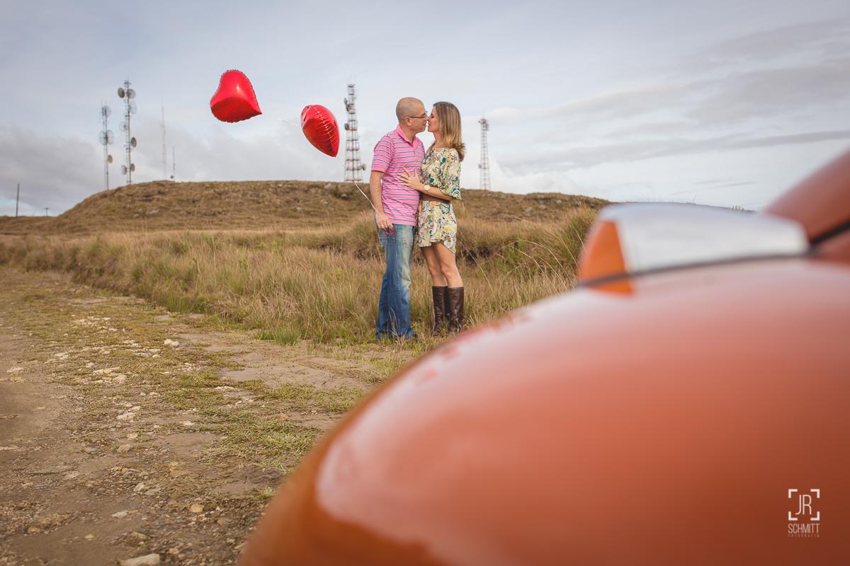 casal com balão de coração e fusca