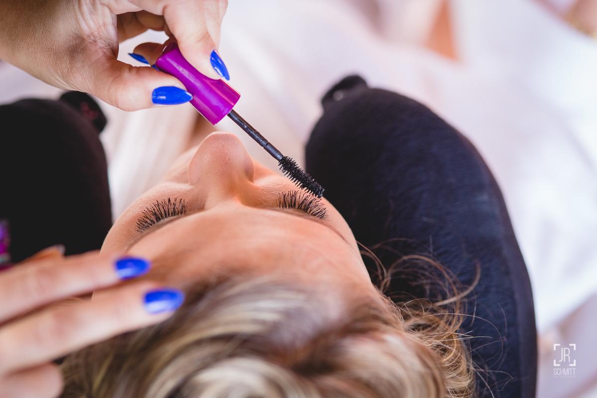 Maquiadora com esmalte azul passando rímel nos cílios da noiva
