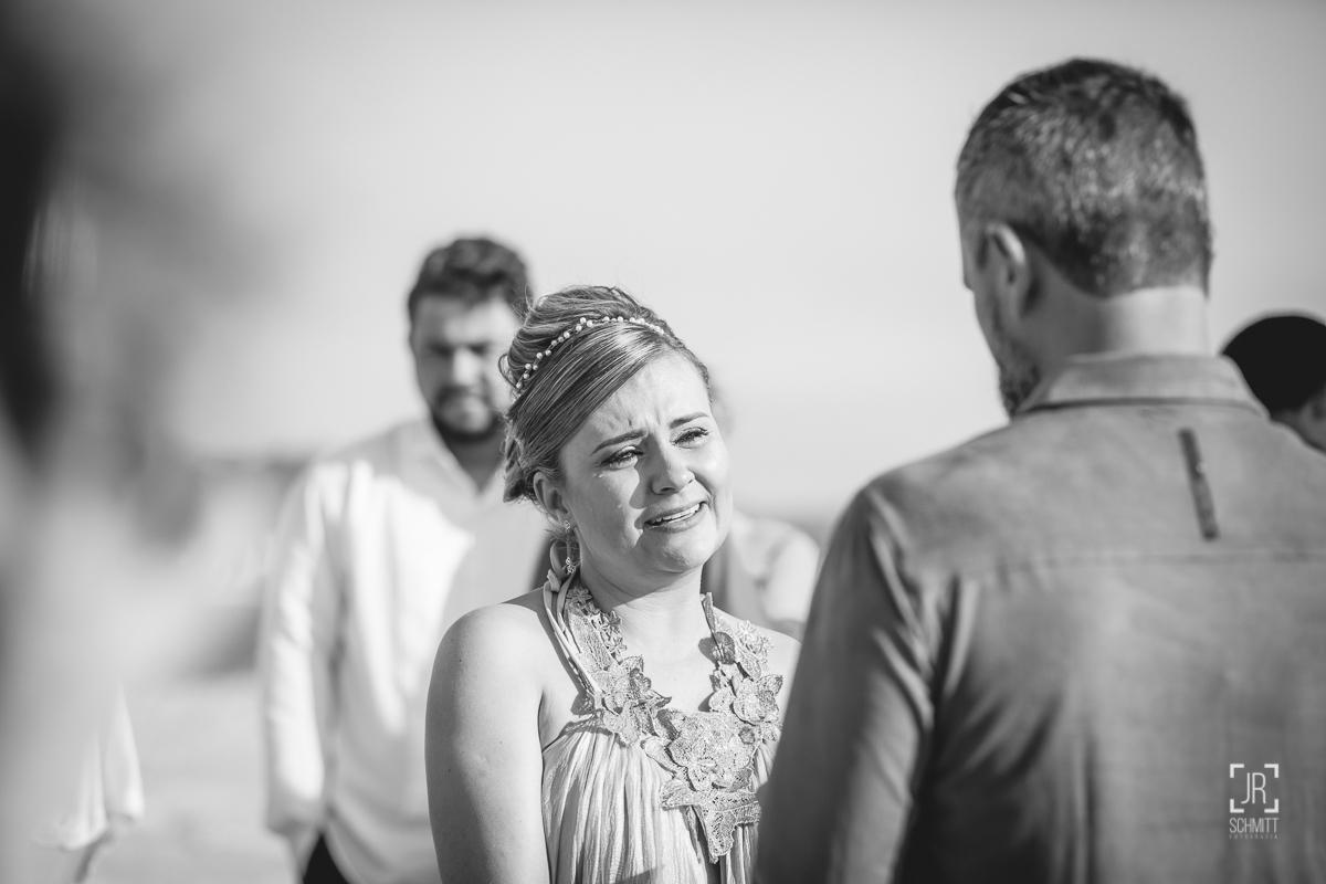Noiva emocionada ouvindo os votos do seu noivo