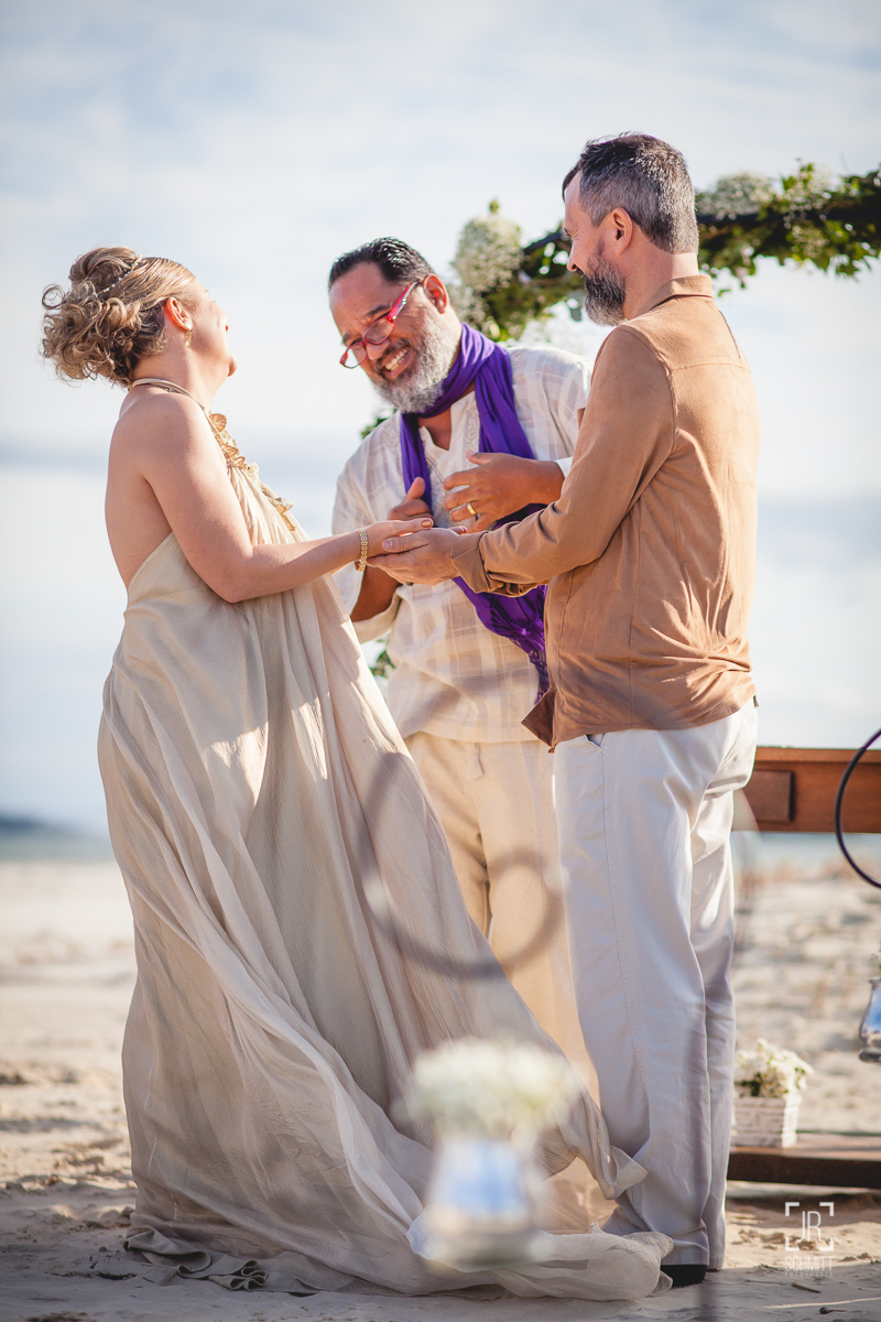 Celebrante sorri com os noivos