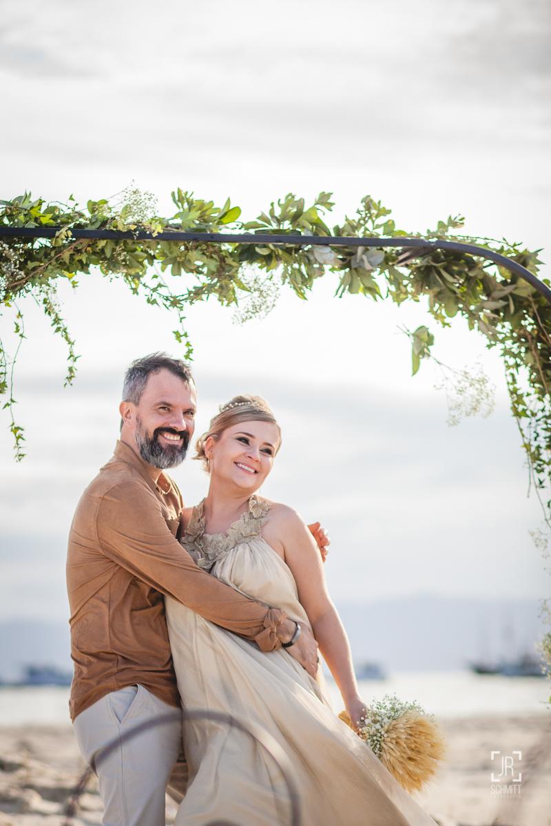 Noivos durante casamento na praia com altar de guirlanda