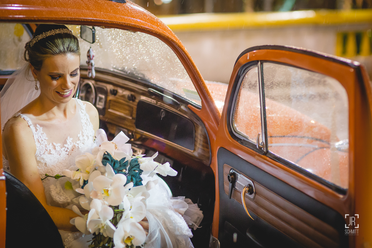 noiva chegando na igreja de fusca laranja