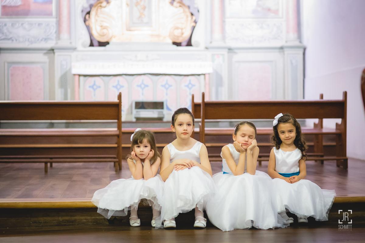 daminhas sentadas no canto da igreja observam a cerimônia