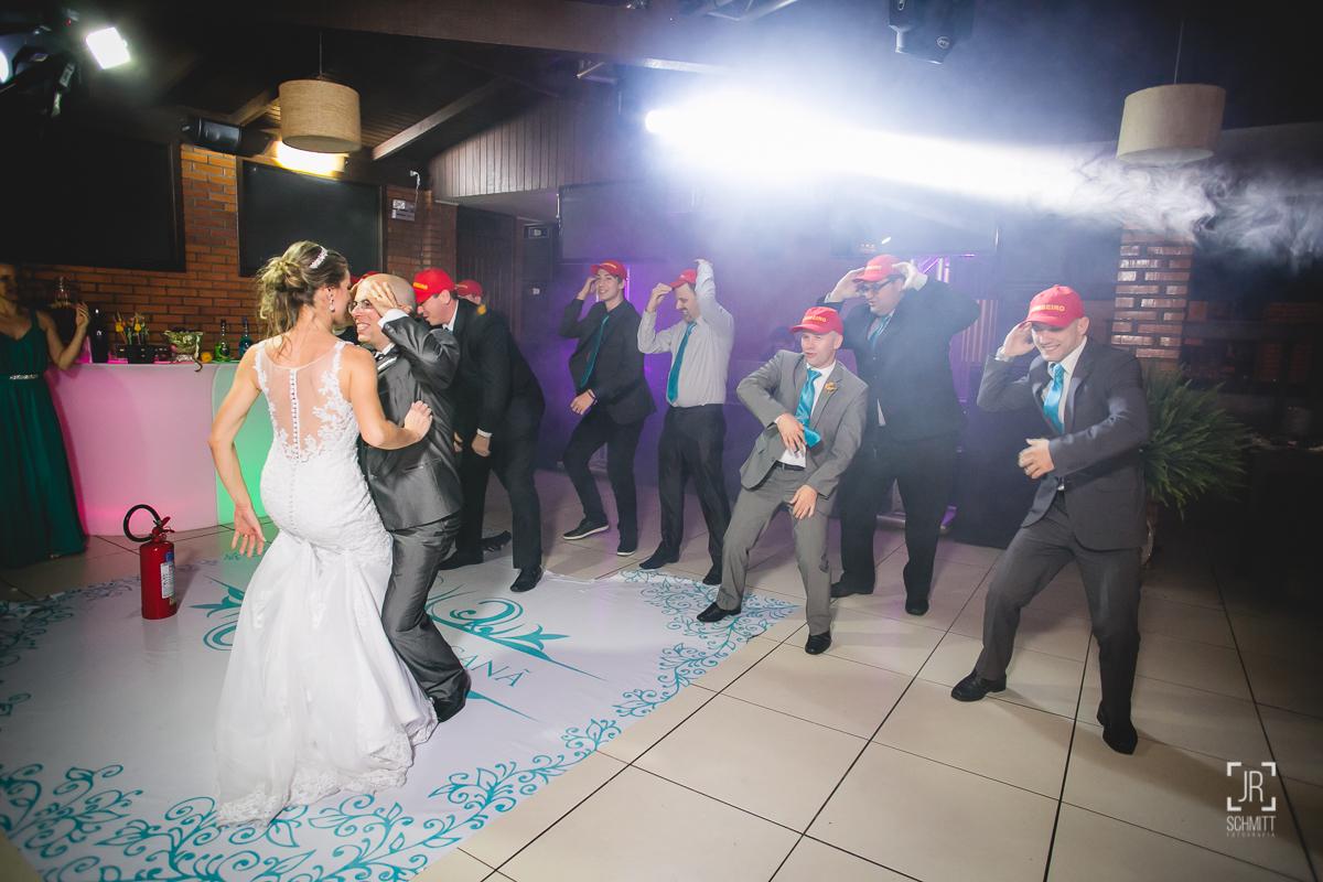 os padrinhos fizeram uma dança surpresa, com bonés de bombeiro