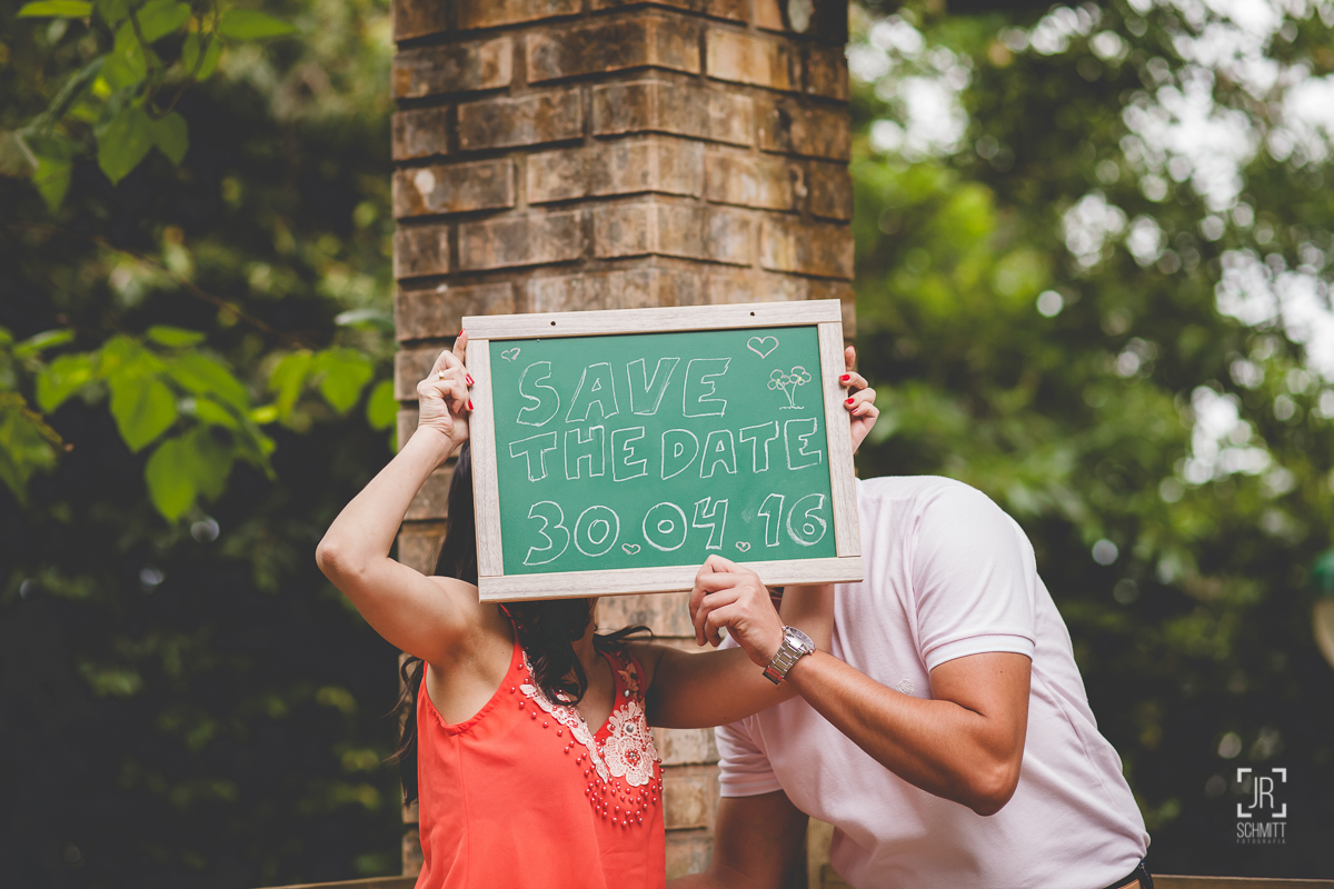beijo escondido atrás da plaquinha do save-the-date