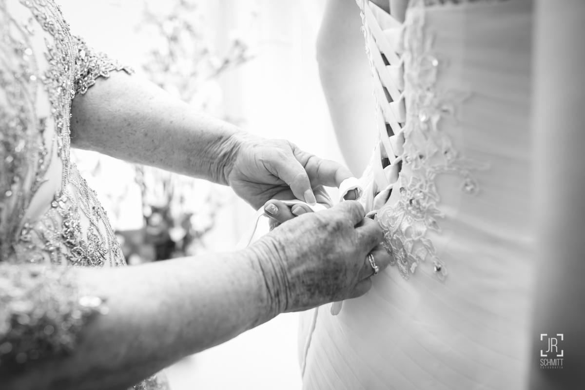 mãe da noiva amarrando o vestido