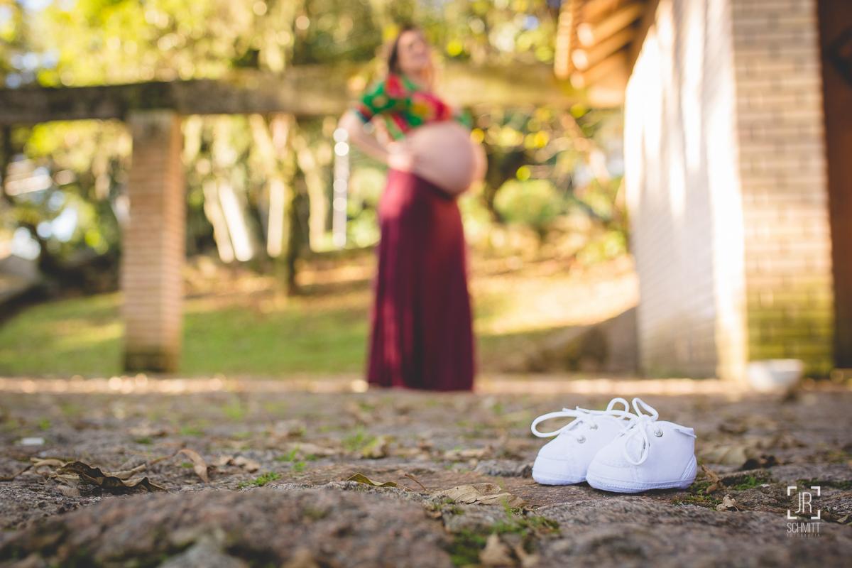 Sapatinho do bebê com gestante ao fundo