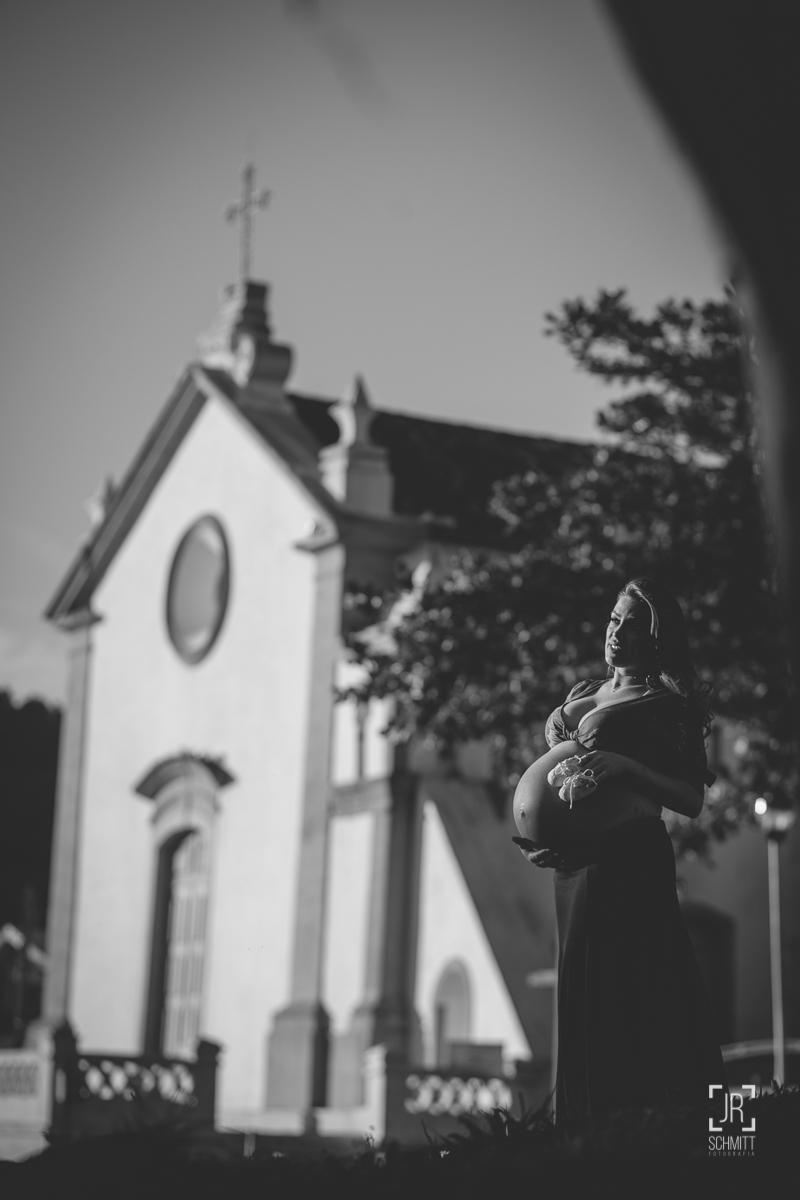 Gestante em preto e branco com a igreja de Santo Antônio de Lisboa ao fundo