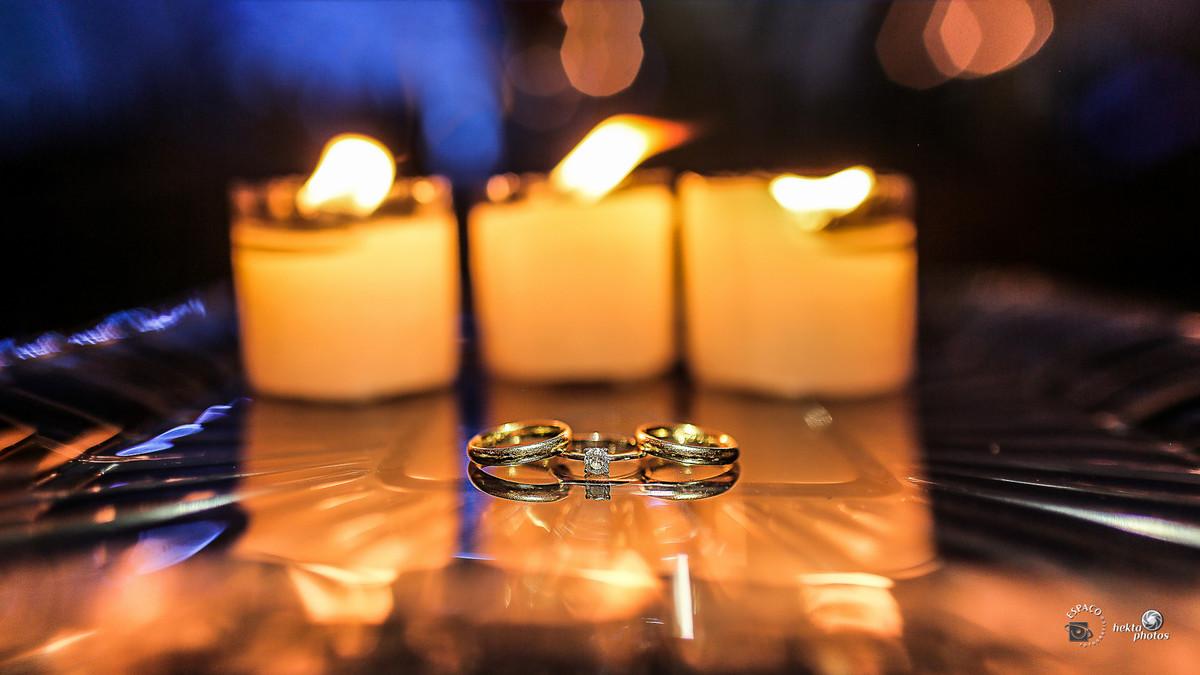 As alianças unidas em frente a velas acesas preparadas para o casamento por Espaço Fotográfico