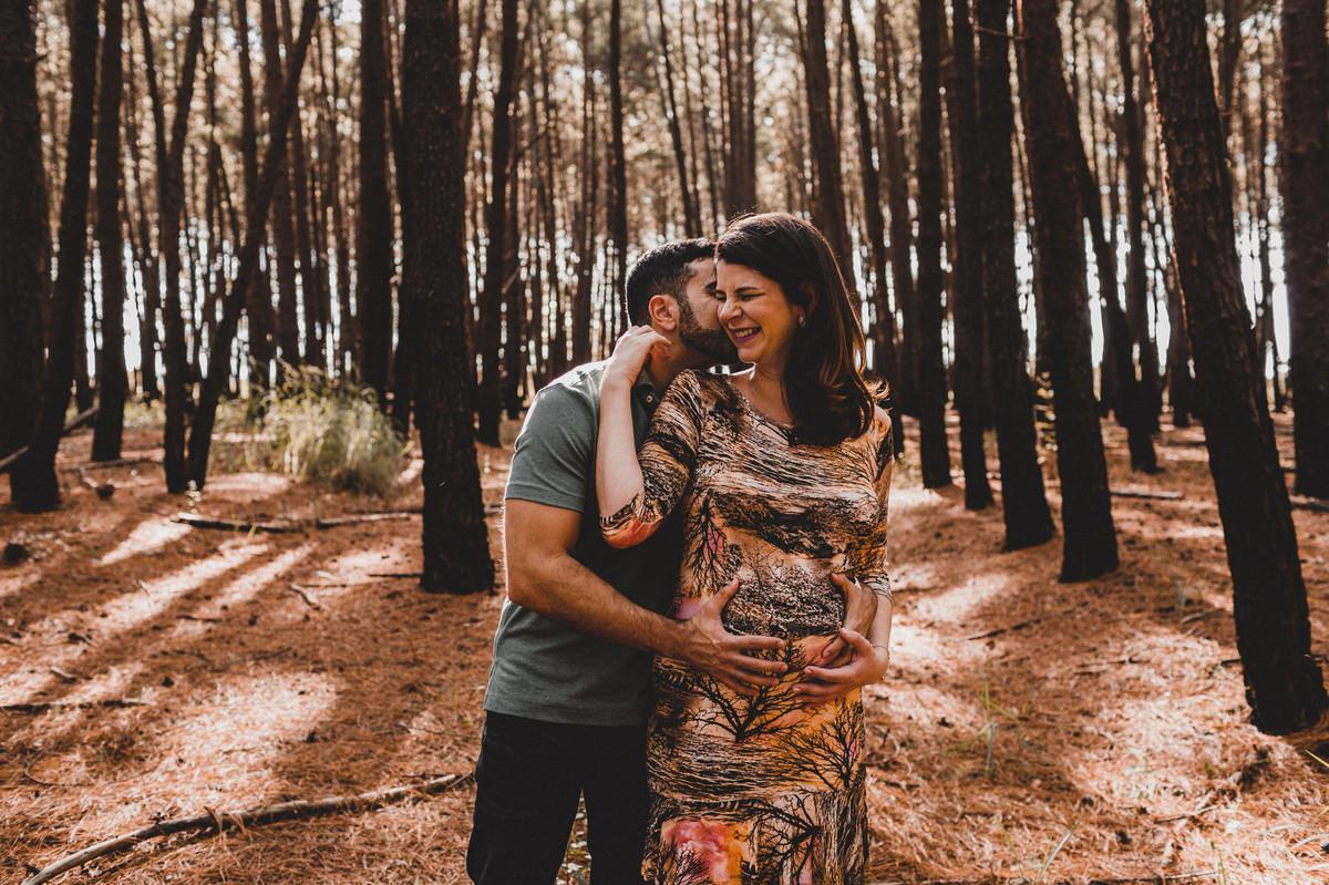 Ensaio de Gestante Ana Flávia e Guilherme. Casal abraçado sorrindo em floresta. Foto feita pelo fotógrafo Gabriel Pelaquim.