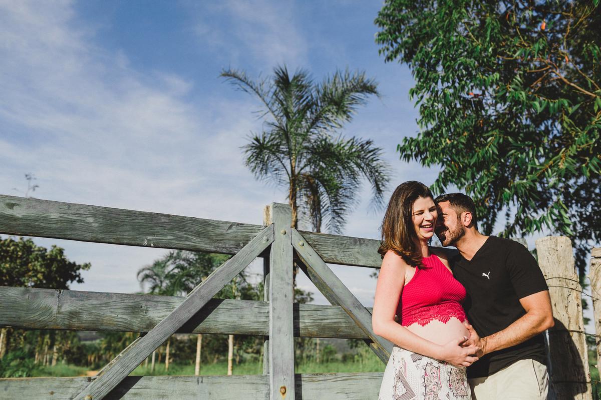 Ensaio de Gestante Ana Flávia e Guilherme. Casal abraçado sorrindo em portão de fazenda em Brasília. Foto feita pelo fotógrafo Gabriel Pelaquim.