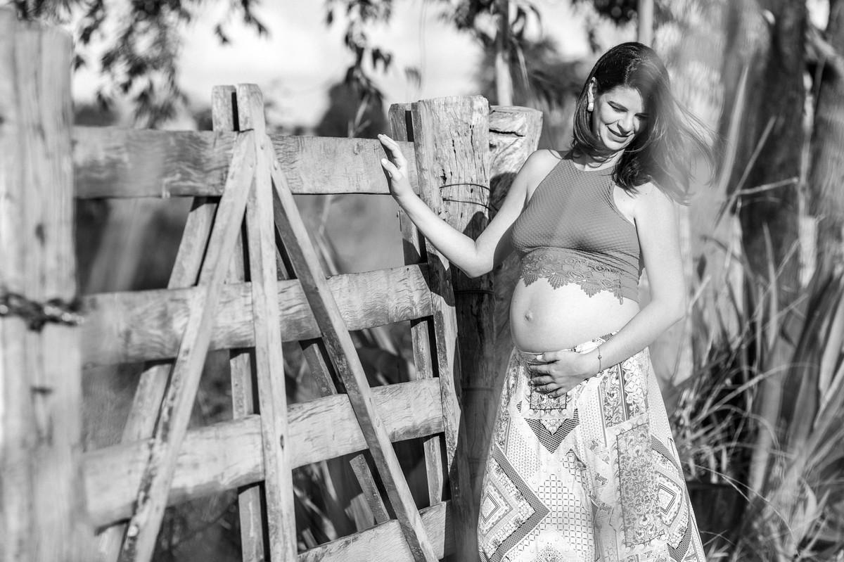 Ensaio de Gestante Ana Flávia e Guilherme. Mulher grávida em portão de fazenda em Brasília. Foto feita pelo fotógrafo Gabriel Pelaquim.