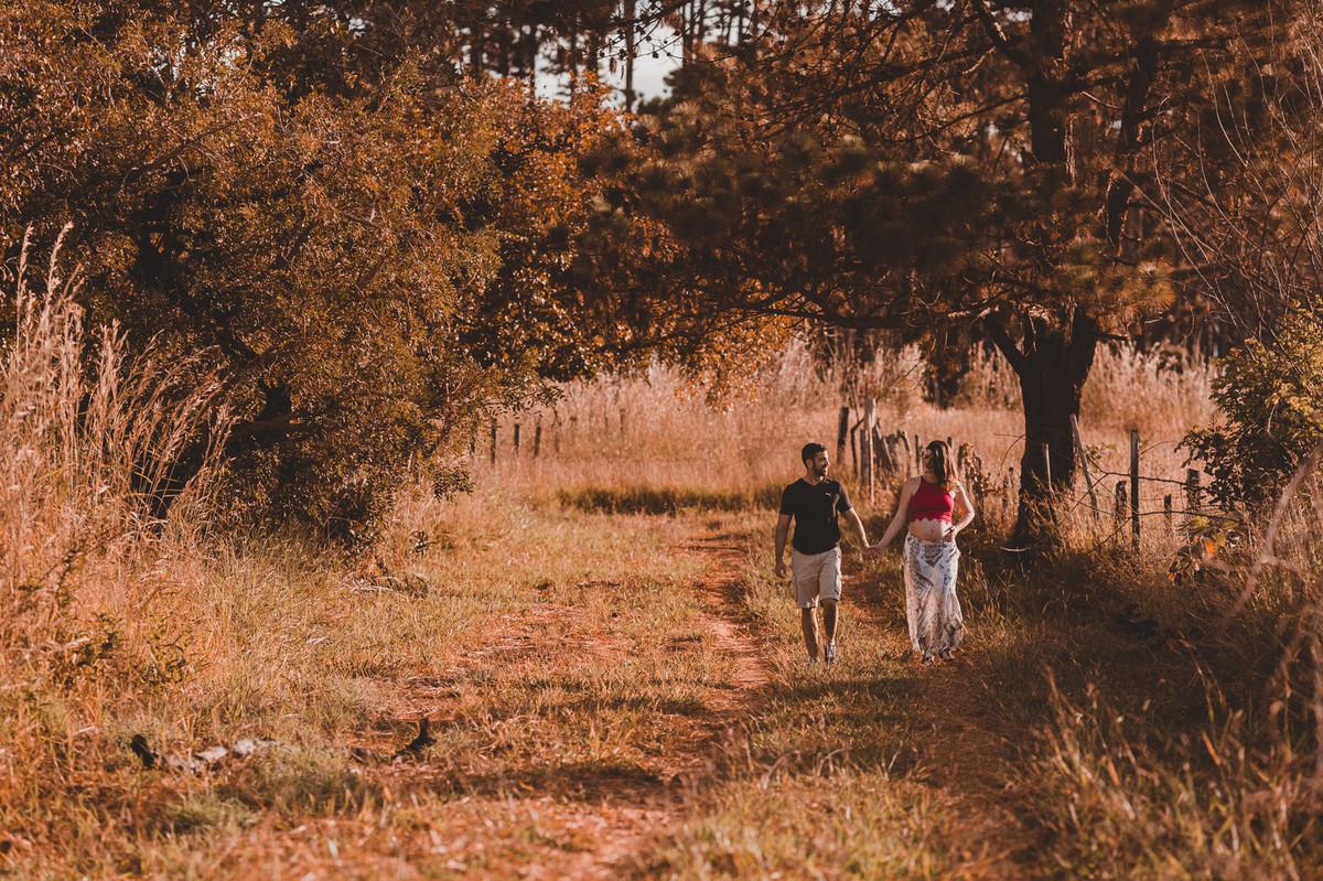 Ensaio de Gestante Ana Flávia e Guilherme. Casal andando de mãos dadas em um matagal em Brasília. Foto feita pelo fotógrafo Gabriel Pelaquim.