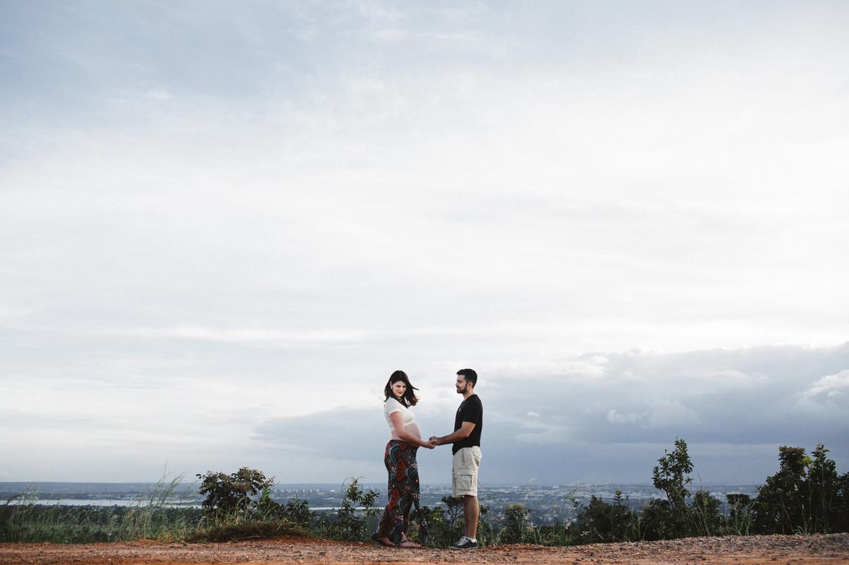 Ensaio de Gestante Ana Flávia e Guilherme. Casal de mãos dadas no mato em Brasília. Foto feita pelo fotógrafo Gabriel Pelaquim.