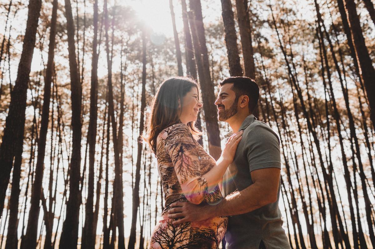 Ensaio de Gestante Ana Flávia e Guilherme. Casal abraçado sorrindo em uma floresta. Foto feita pelo fotógrafo Gabriel Pelaquim.