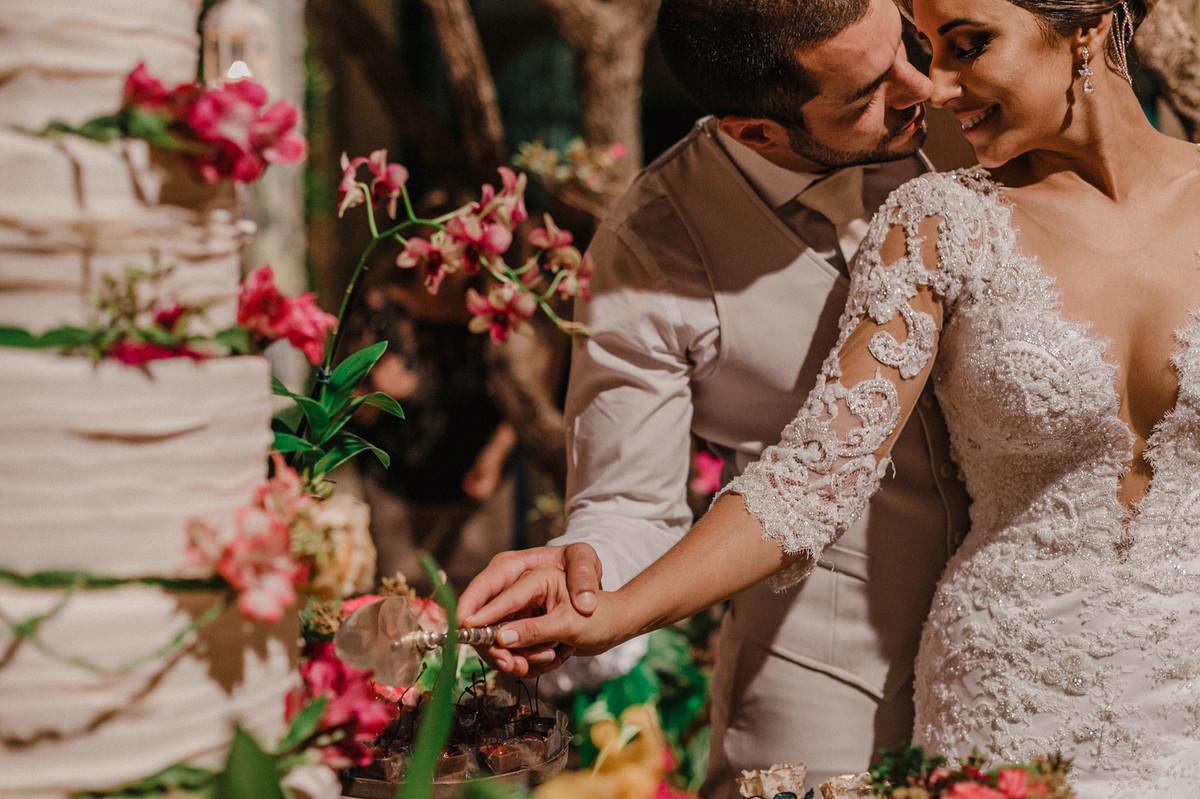 Noivos cortando o bolo no Villa Giardini. Foto pelo fotógrafo de casamento Gabriel Pelaquim.