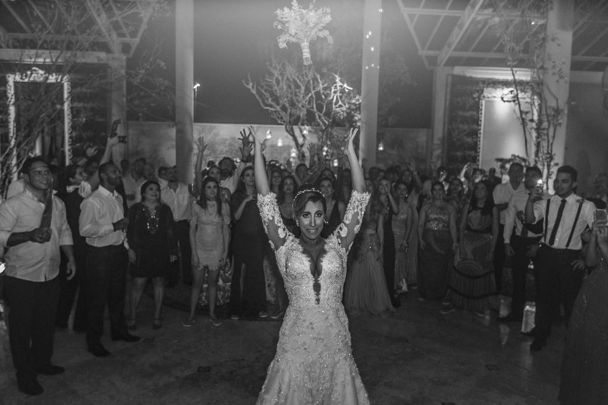 Noiva jogando o buquê na festa de casamento no Villa Giardini. Foto pelo fotógrafo de casamento Gabriel Pelaquim.
