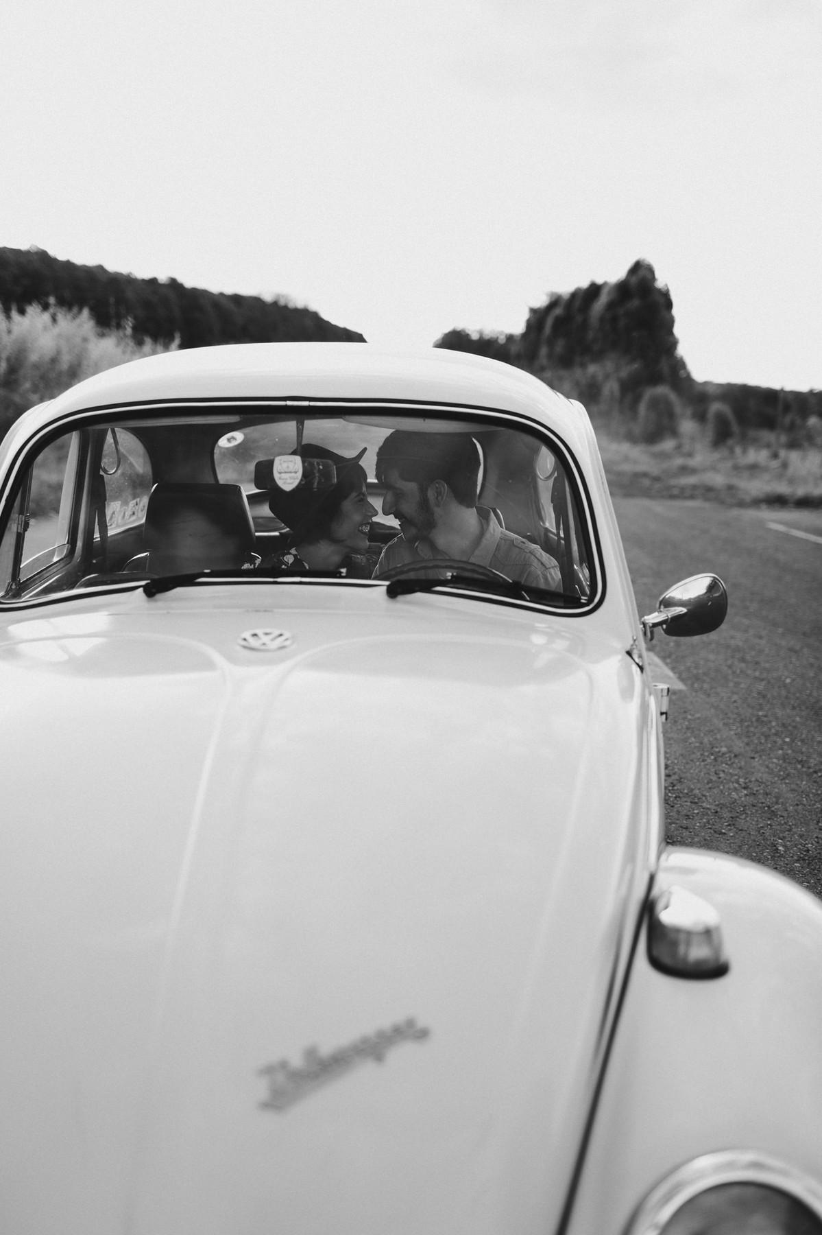 Casal sorrindo dentro de fusca em Brasília. Foto feita pelo fotógrafo de casamento Gabriel Pelaquim.