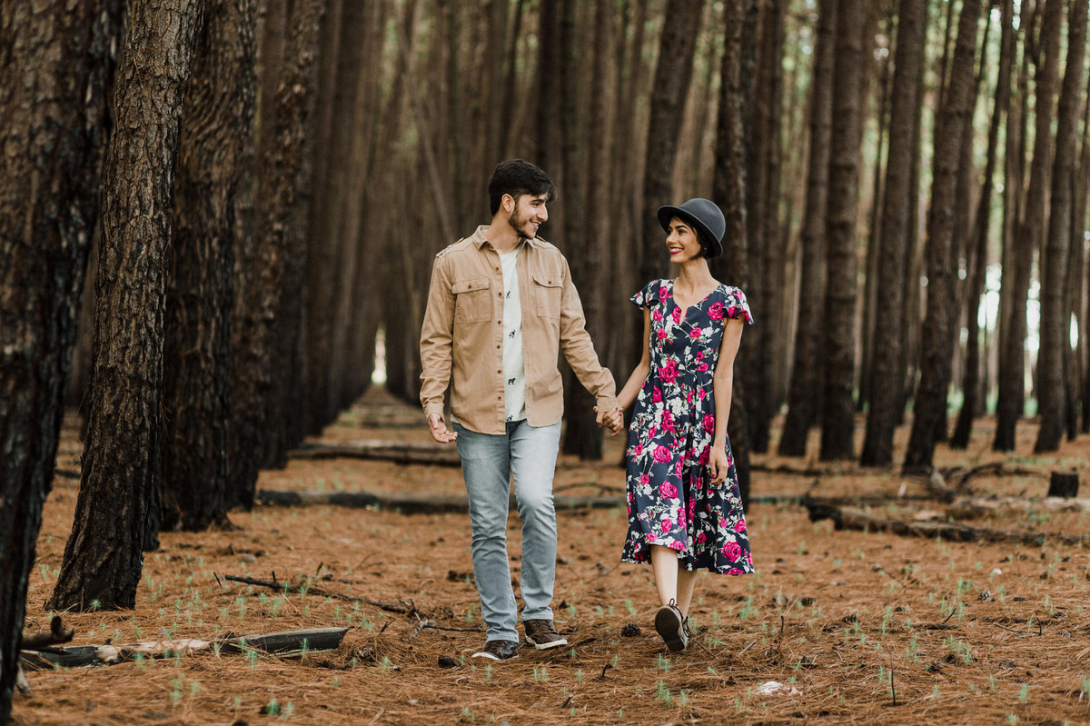 Casal de mãos dadas sorrindo em floresta de pinheiros em Brasília. Foto feita pelo fotógrafo de casamento Gabriel Pelaquim.