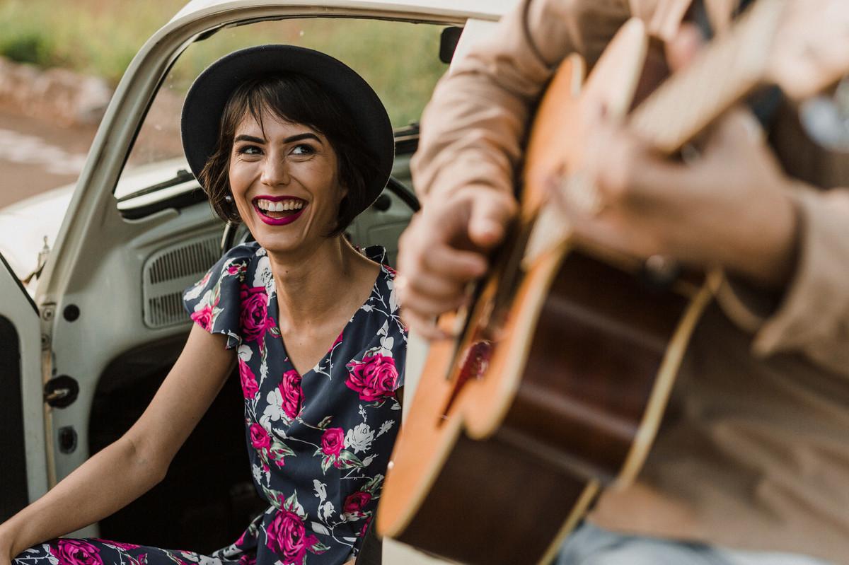 Noiva sorrindo para noivo enquanto ele toca violão. Foto feita pelo fotógrafo de casamento Gabriel Pelaquim.