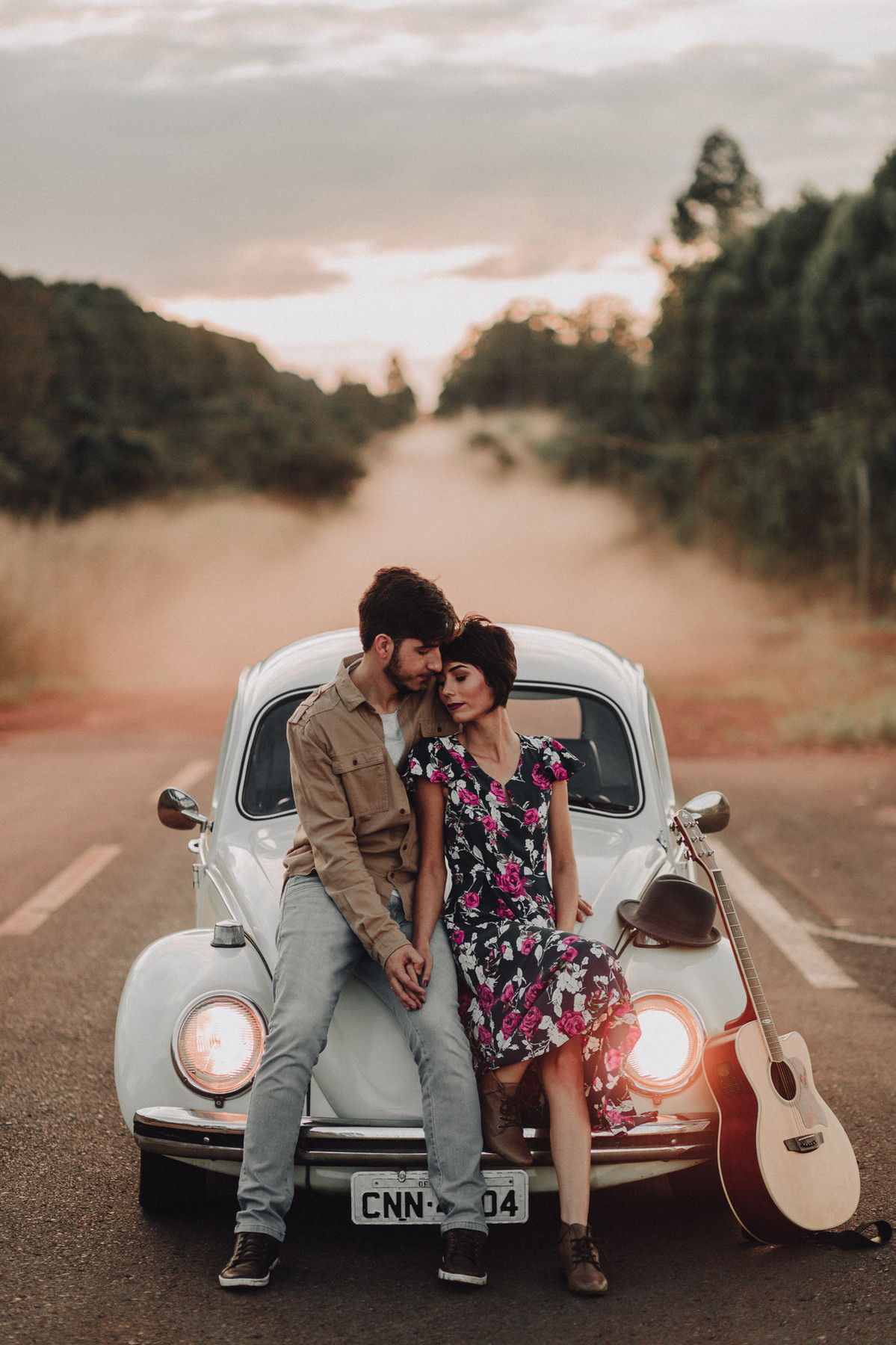 Casal abraçado em capô de fusca em estrada em Brasília. Foto feita pelo fotógrafo de casamento Gabriel Pelaquim.