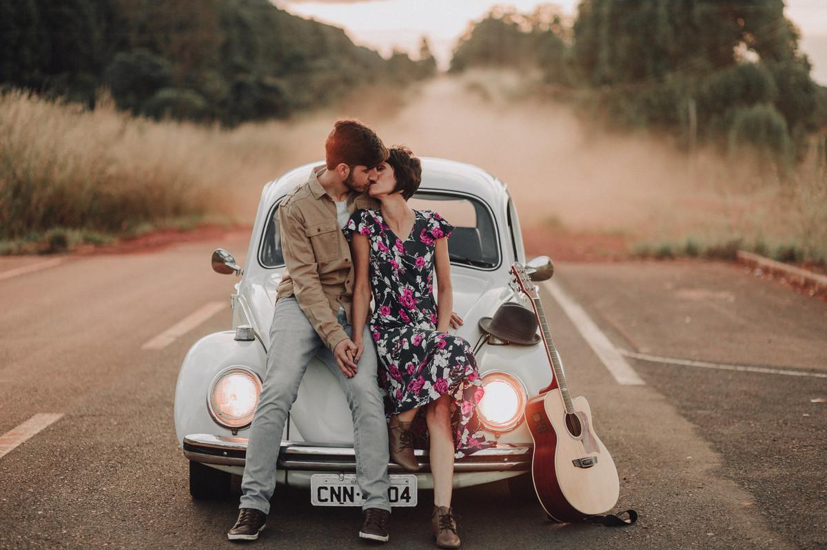 Casal abraçado se beijando no capô de um fusca em estrada em Brasília.  Foto feita pelo fotógrafo de casamento Gabriel Pelaquim.