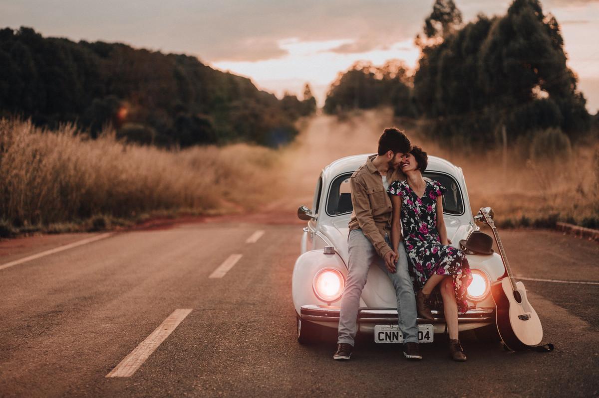Casal sentado em capô de fusca em estrada em Brasília.  Foto feita pelo fotógrafo de casamento Gabriel Pelaquim.
