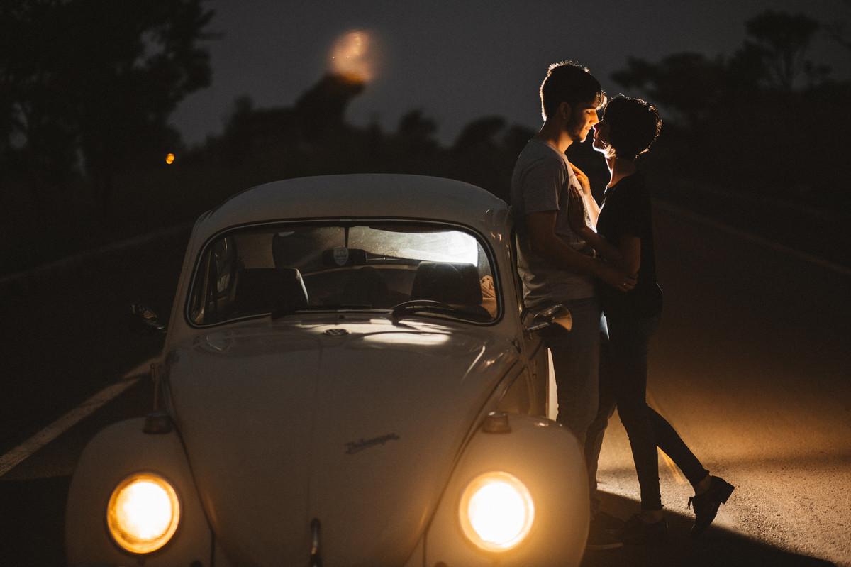 Casal abraçado encostado em fusca em estrada em Brasília.  Foto feita pelo fotógrafo de casamento Gabriel Pelaquim.