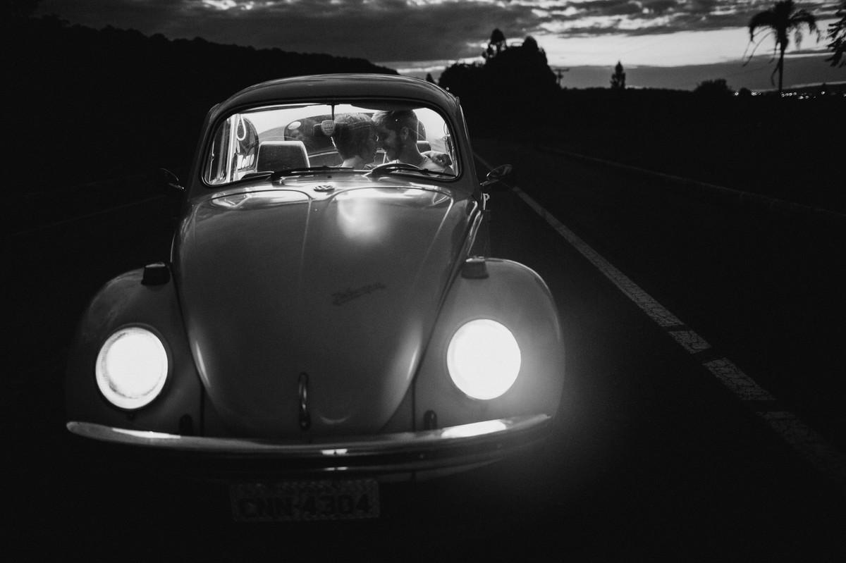 Casal dentro de fusca em estrada em Brasília.  Foto feita pelo fotógrafo de casamento Gabriel Pelaquim.
