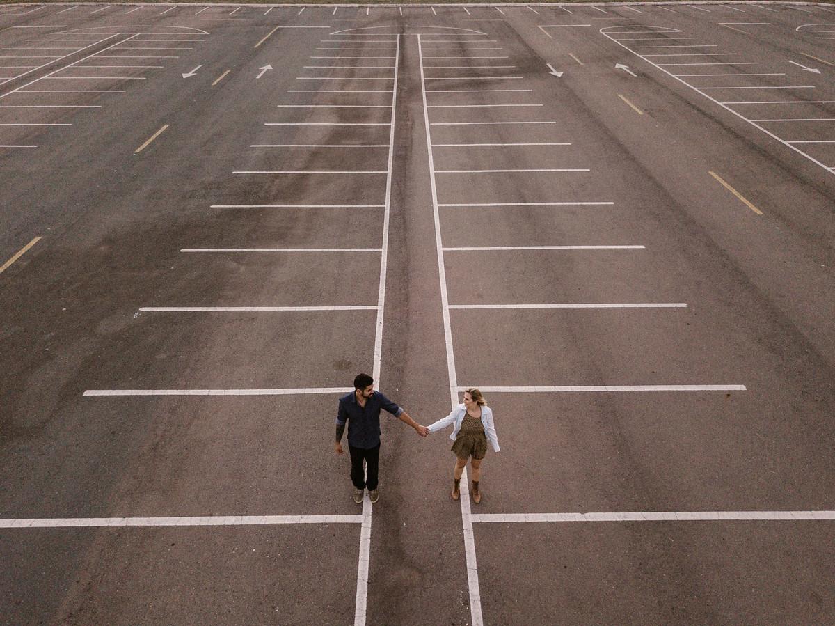 Casal de mãos dadas em estacionamento em Brasília. Foto feita pelo fotógrafo de casamento Gabriel Pelaquim.
