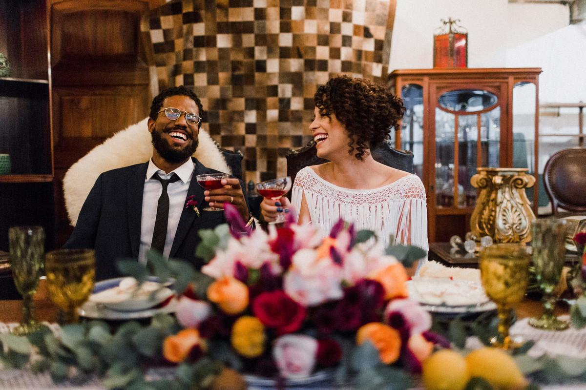 Noivos sentados à mesa.  Foto feita pelo fotógrafo de casamento Gabriel Pelaquim.