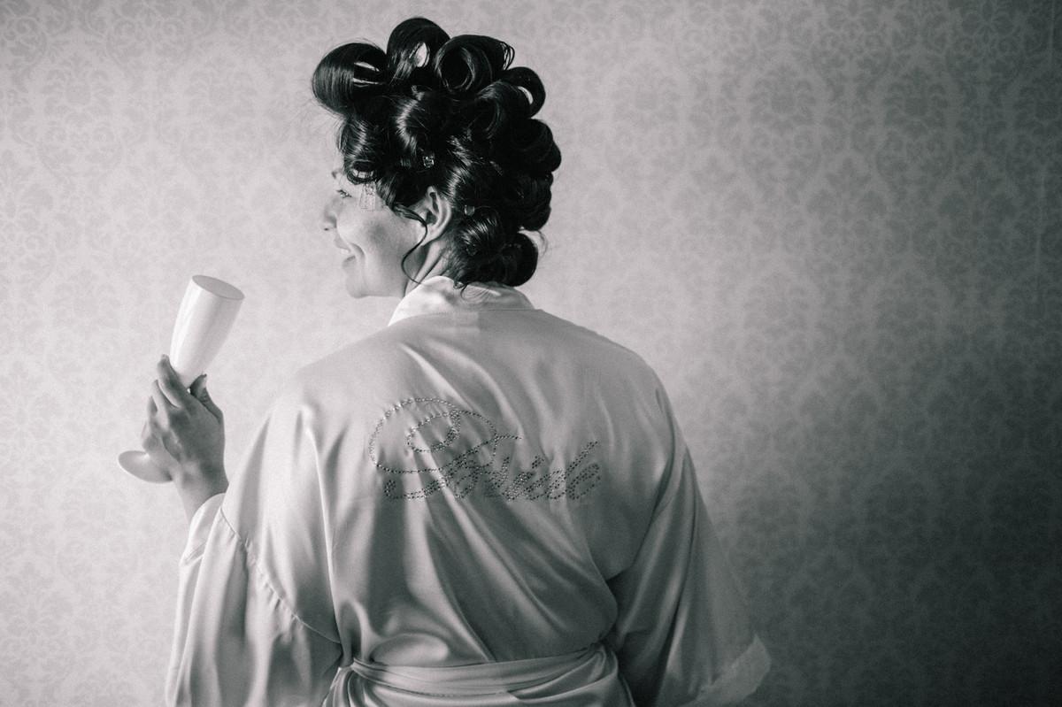 Foto da noiva com champanhe e luz de janela