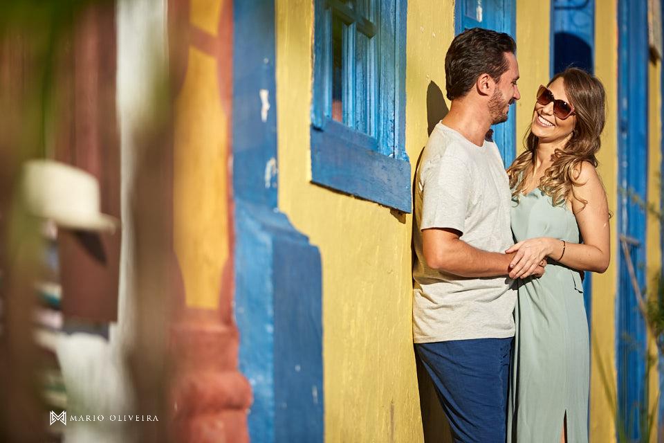 casal abraçado sorrindo em frente a uma casa amarela