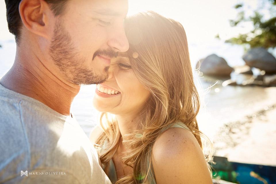 casal abraçado sorrindo de olhos fechados em contra luz com flare