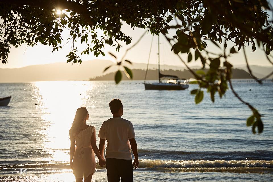 casal de mãos dadas de frente para o mar em baixo de uma arvore no por do sol