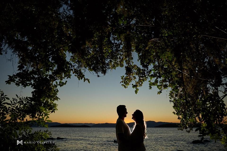 casal abraçado se beijando e em baixo de uma árvore na frente do mar no por do sol