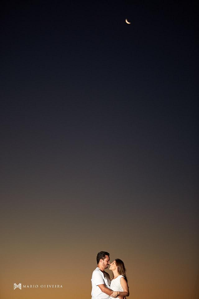 casal abraçado se beijando e em baixo de uma árvore na frente do mar no por do sol, lua crescente