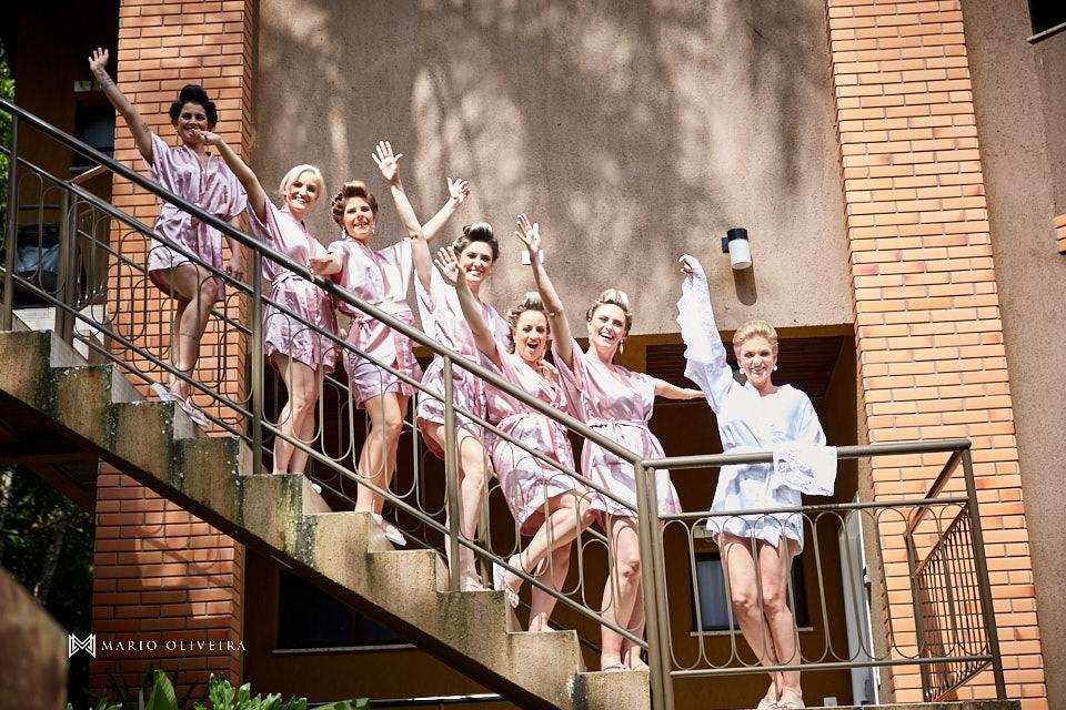 madrinhas e noiva de roupão de braços levantados em uma escada do hotel do making of