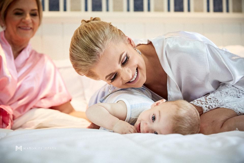 noiva de roupão, sorrindo olhando para bebe deitado na cama no making of