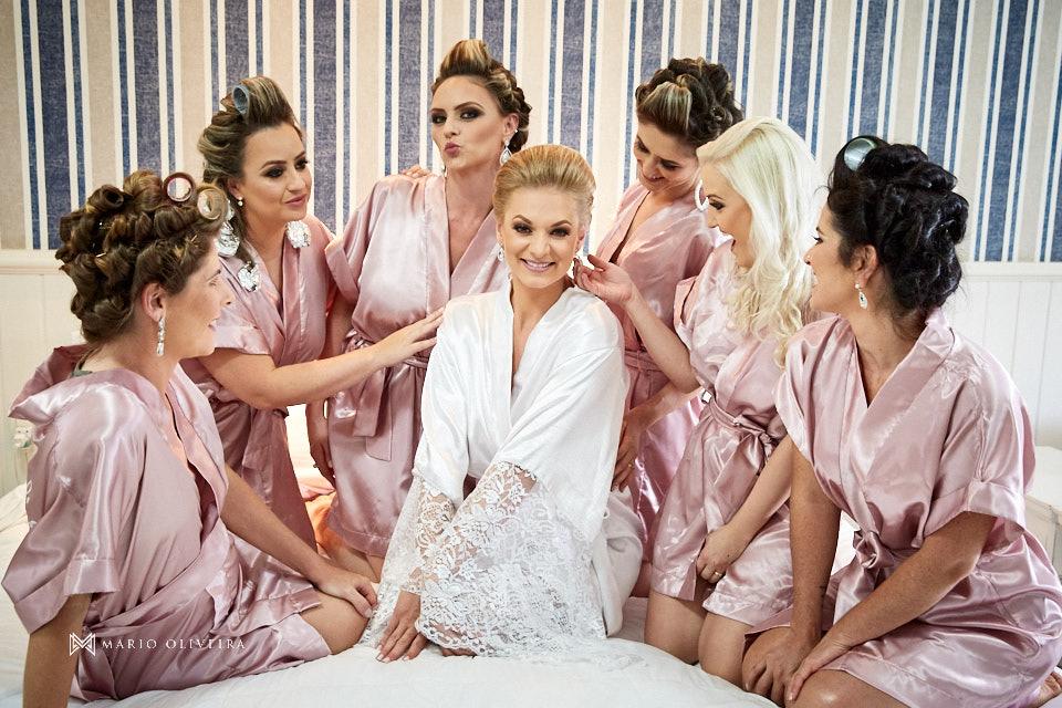 noiva e madrinhas de roupão, ajoelhadas em cima da cama no quarto do hotel do making of