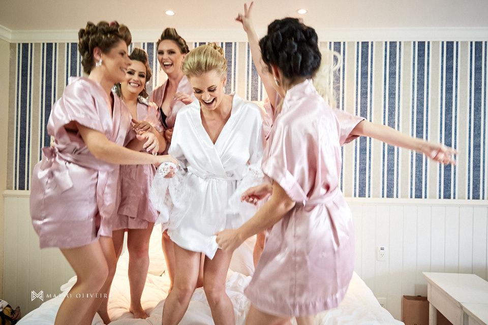 noiva e madrinhas de roupão, pulando e dançando em cima da cama no quarto do hotel do making of