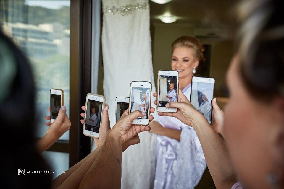 noiva de roupão abraçada no vestido e madrinhas fotografando com seus smartphones no making of